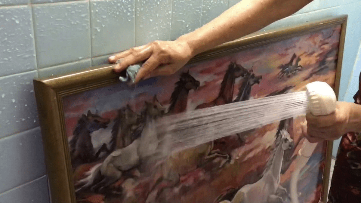 a person washing the oil painting with water