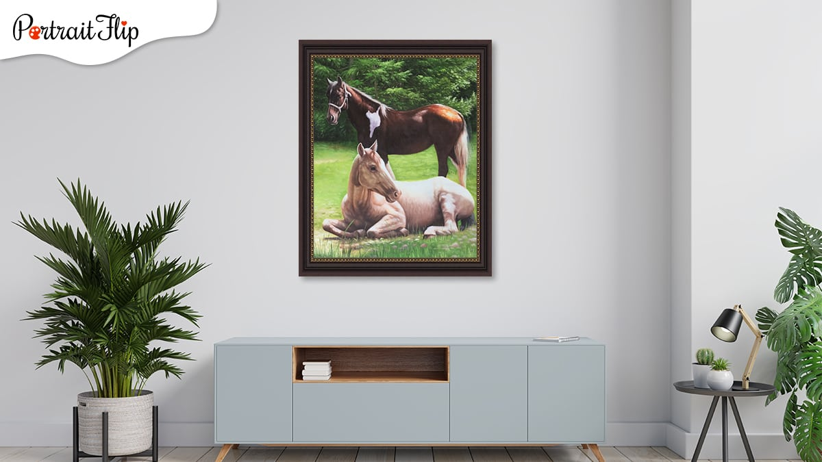 Two horse portraits on a white wall with a table in from and two plants along the sides.