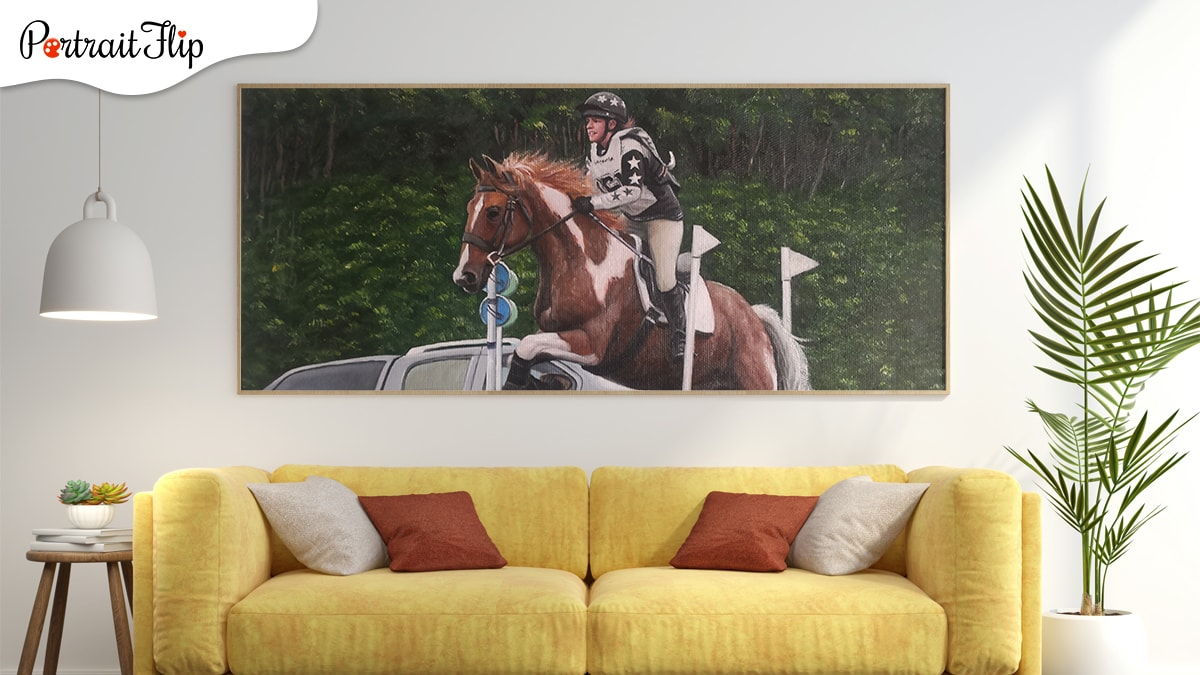 A painting of a woman riding a horse hung on the living room wall with yellow sofa and trees on both the sides of the sofa.