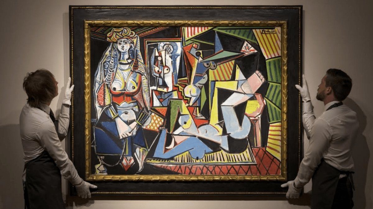 """The painting 'Les Femmes d'Alger (""""Version O""""); by Pablo Picasso is being held at an auction by two men."""