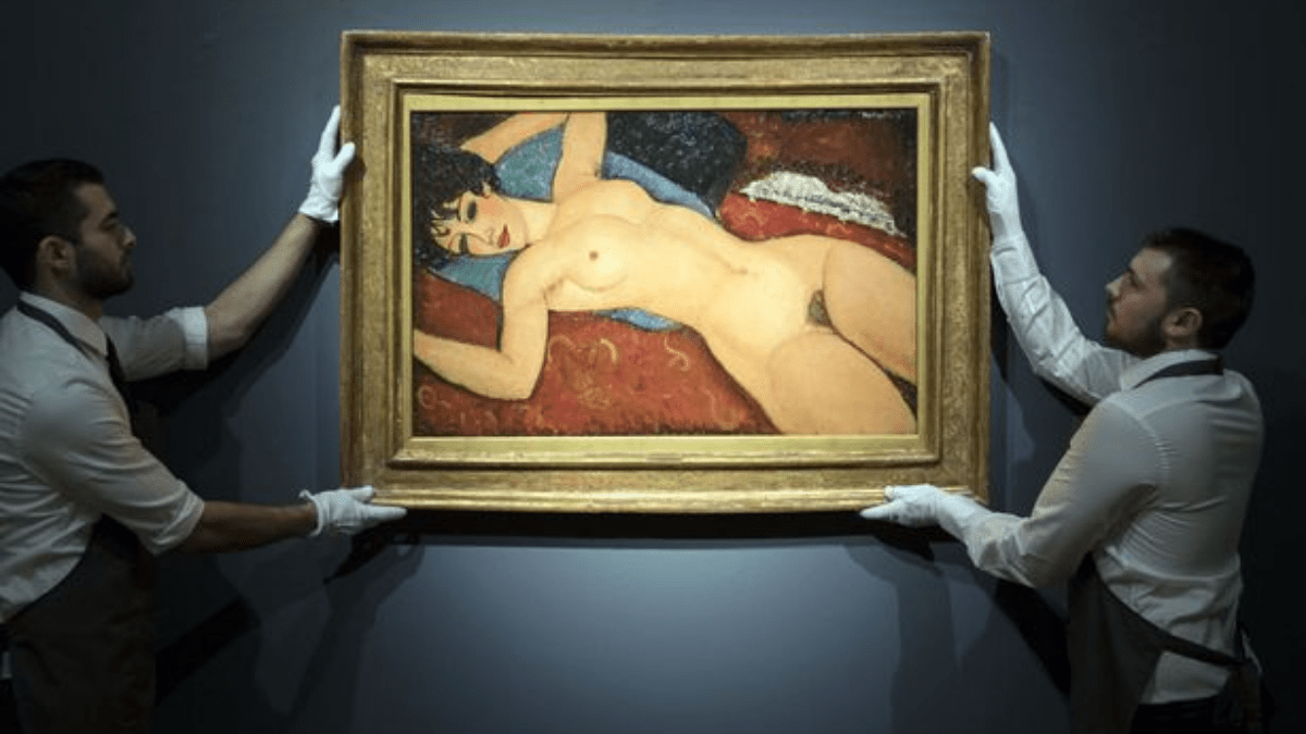 The painting Nu couché by Amedeo Modigliani held by two men at an auction.