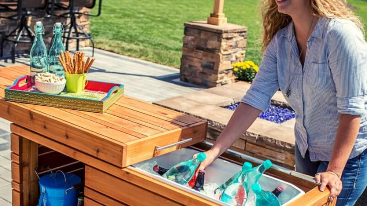 a woman removing drinks form a outdoor cooler that has attached table.