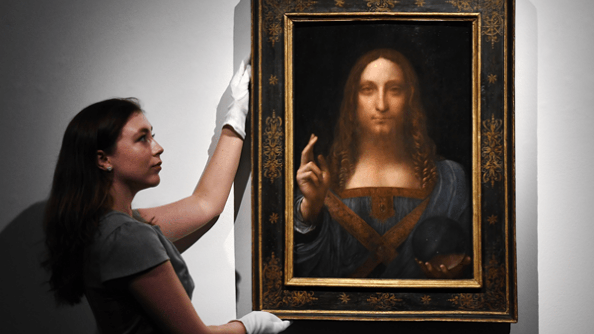 The Most expensive Painting 'Salvator Mundi' being held by girl in the Christie's auction house.