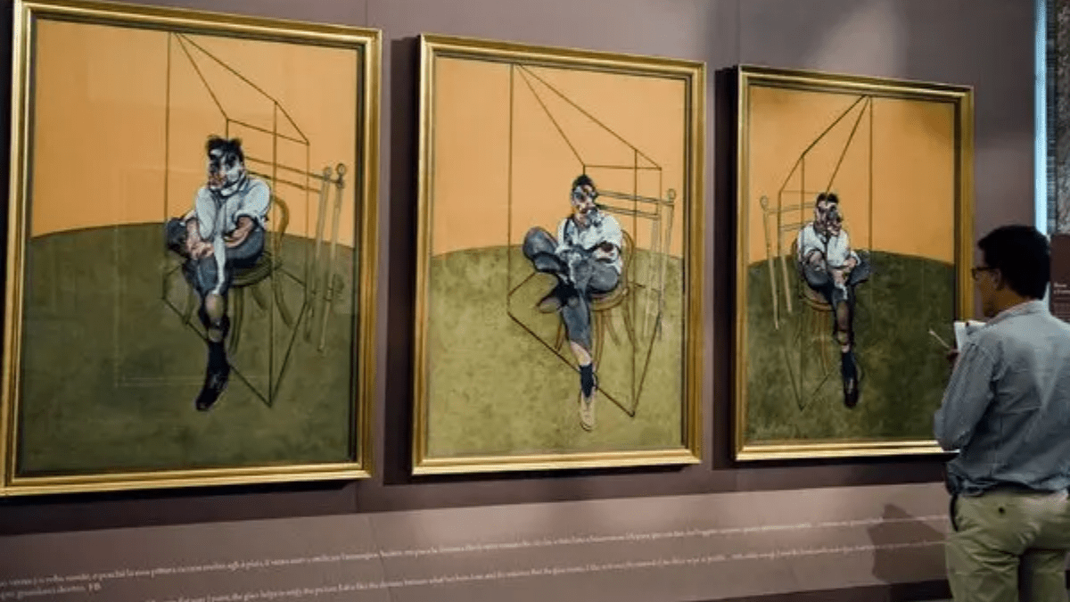 The painting 'Three Studies of Lucian Freud' by Francis Bacon. This triptych is being viewed by a man in a museum.