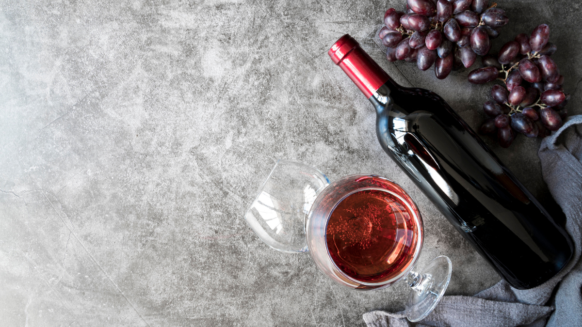 A delicious glass of wine is kept on the table with some grapes around it.