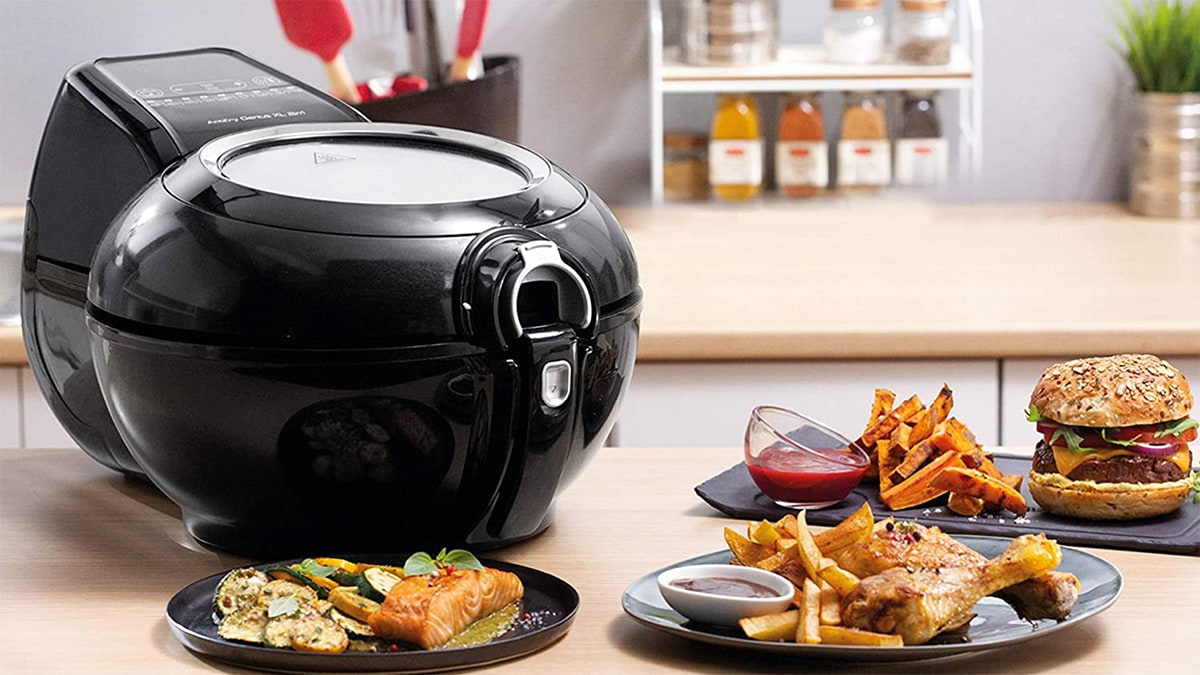 A black air fryer on a table. beside it is fried food made with the air fryer.