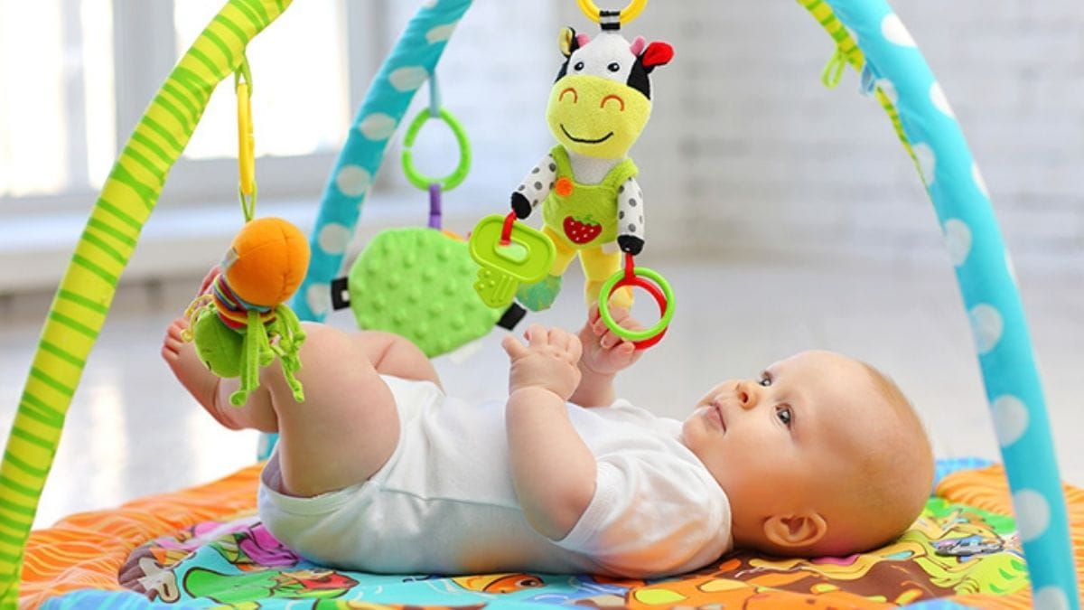 a baby playing with the Baby gym set.