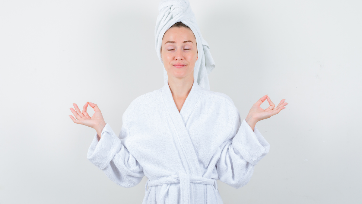A girl in a bathrobe is smiling and meditating in a standing position.