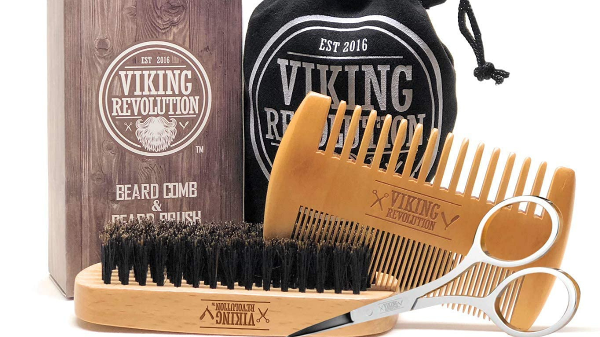 A beard comb and brush set on the white surface.