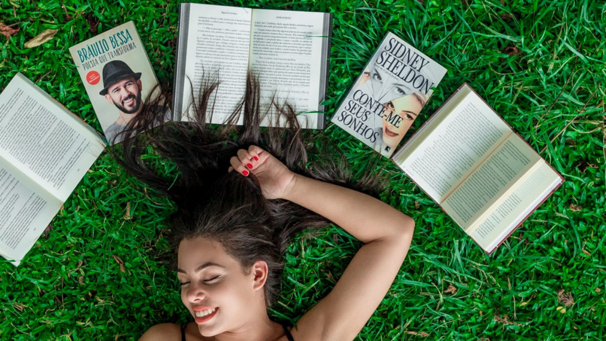 A girl lying in the garden and there are books over her head.