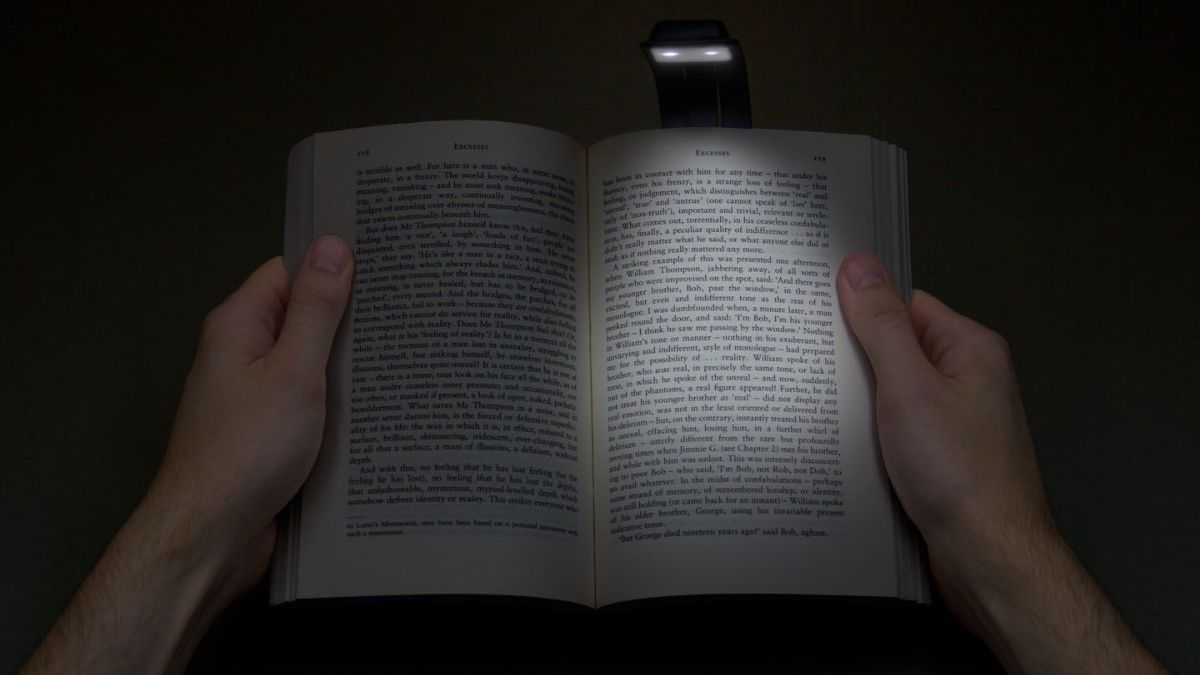 a person reading a book in darkness with the help of booklight.