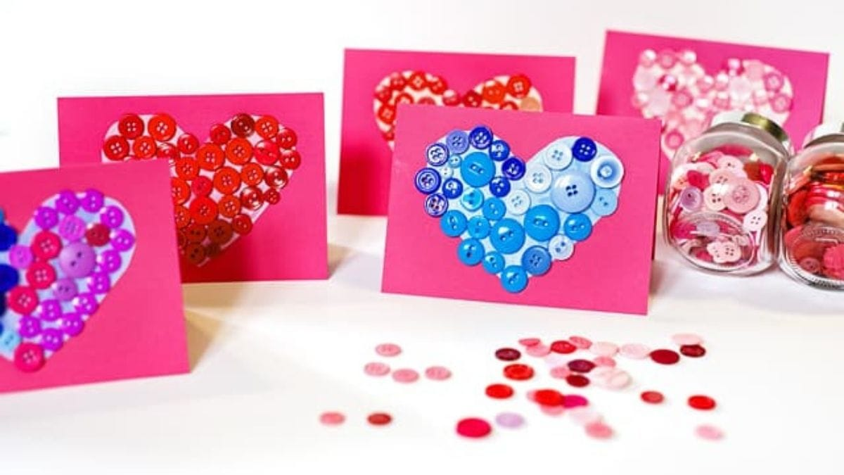 Love letters embellished with buttons in heart shape are placed on a white background.