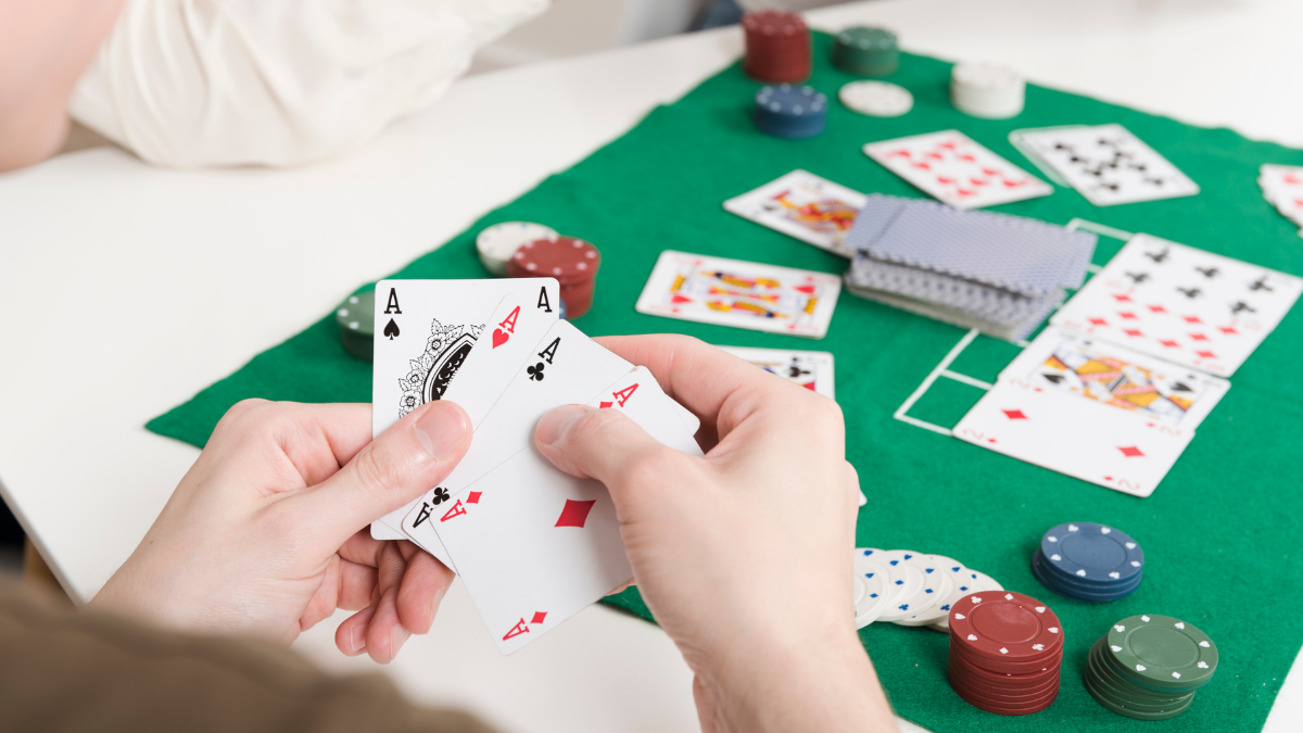 Three ace cards is shown on a boy's hand.
