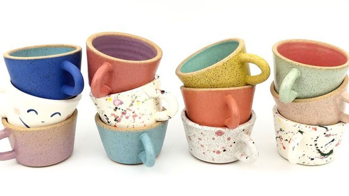 Multiple ceramic mugs are placed on a white background. These ceramic mugs are in multiple colors.