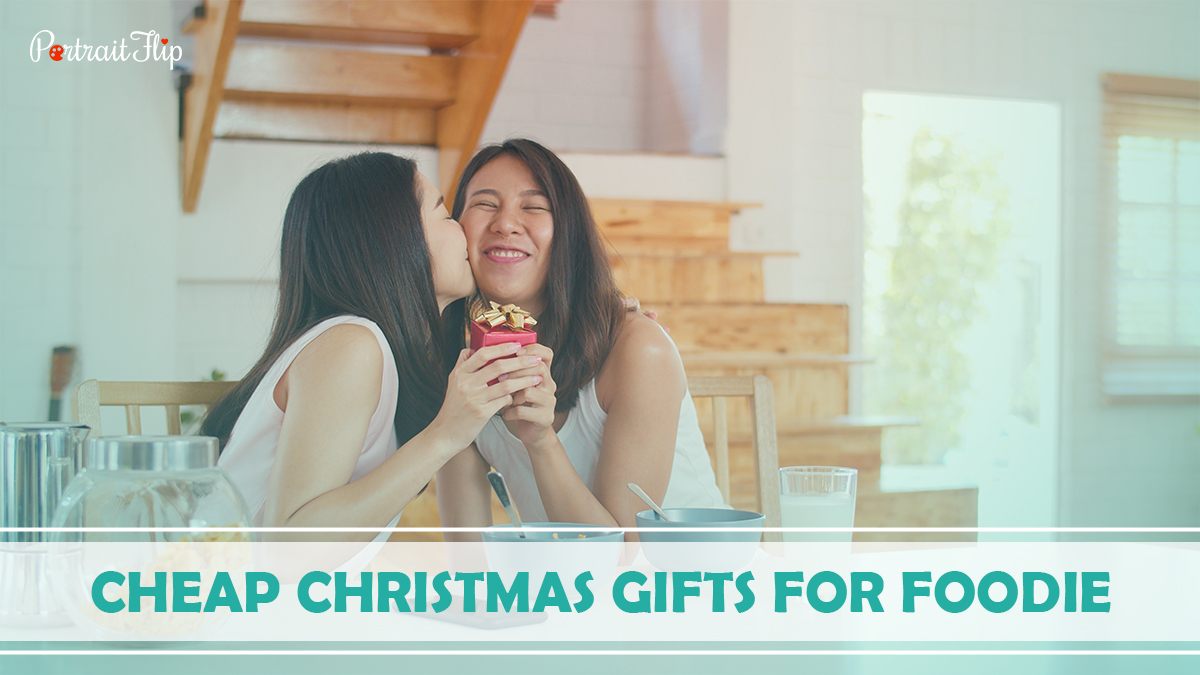 Cheap Christmas Gifts For Foodie: A girl is kissing her best friend by giving her Christmas gifts.