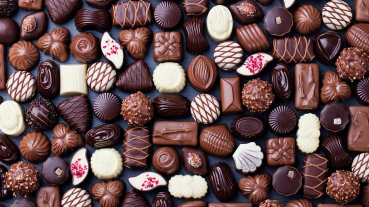 Some delicious chocolates in different shapes are placed on a brown background.