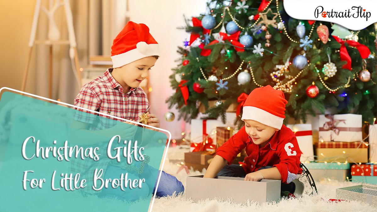 Christmas gifts ideas for little brothers: two brothers sitting by a decorated Christmas tree are opening a Christmas present