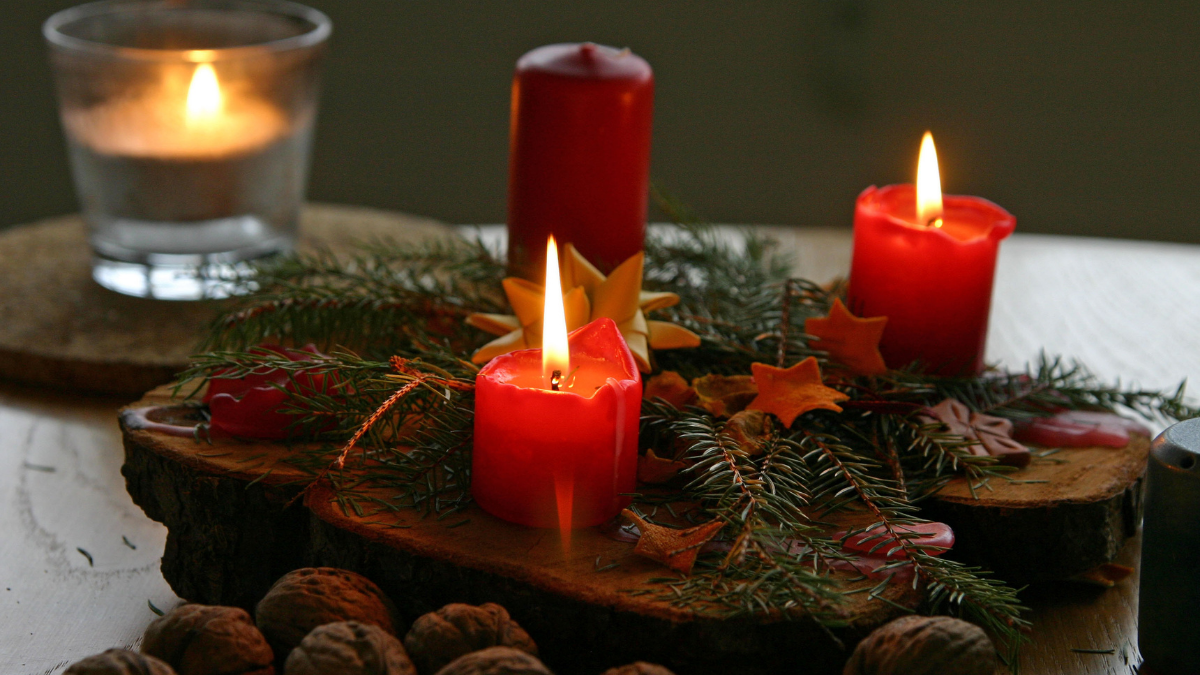 Three red colored Christmas candles are placed on the wooden surface with some leaves around them.