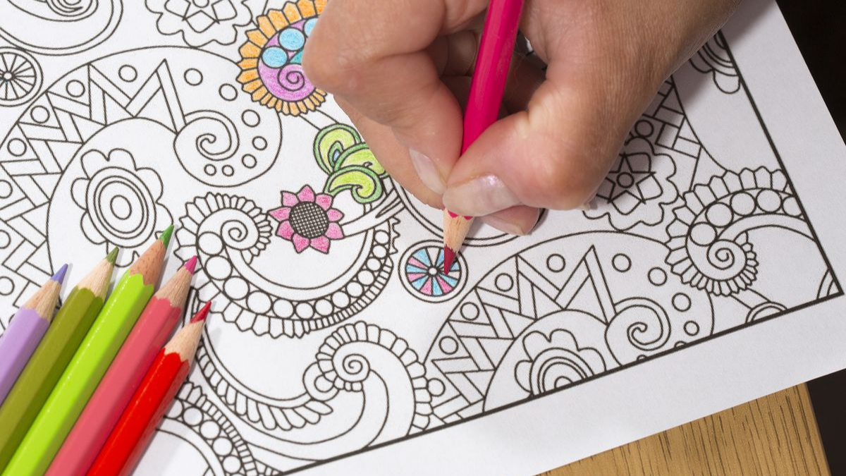 A girl is coloring the mandala color book.