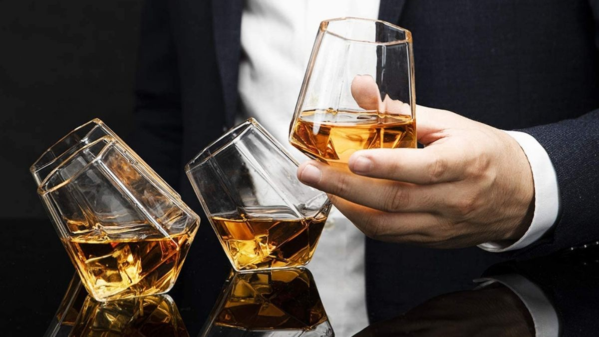 A man holding a diamond whiskey glass in his hand, while other two diamond whiskey glasses are on the table.