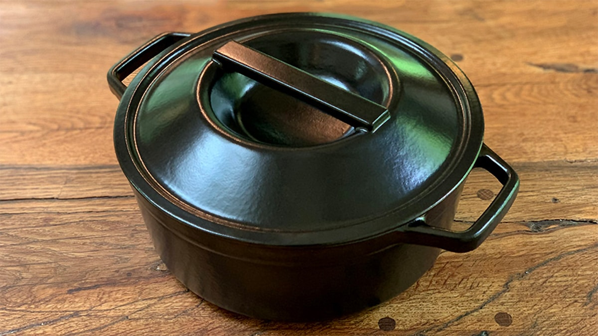 a black Dutch oven on a brown table