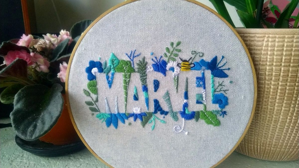 A embroidery marvel hoop art is placed beside the artificial plant in the living area.