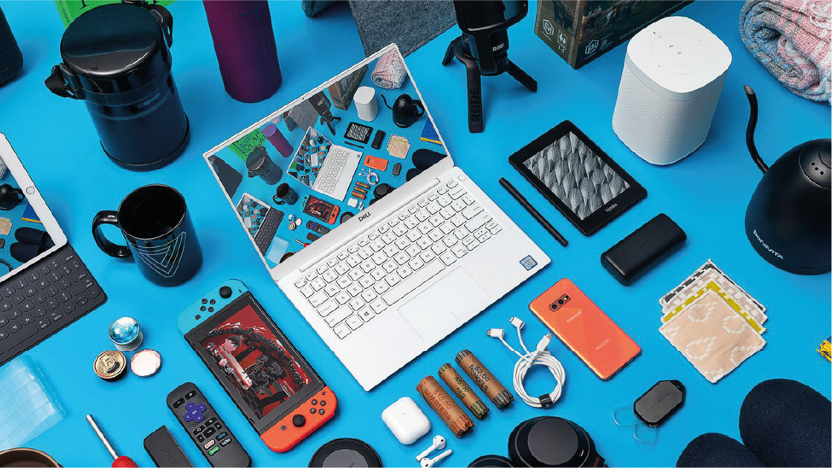 various gadgets including laptop, phone, tablet, remote, nintendo switch, smart cup, speaker, USB cable, power bank, stylus, earbuds, batteries, humidifier against blue background.