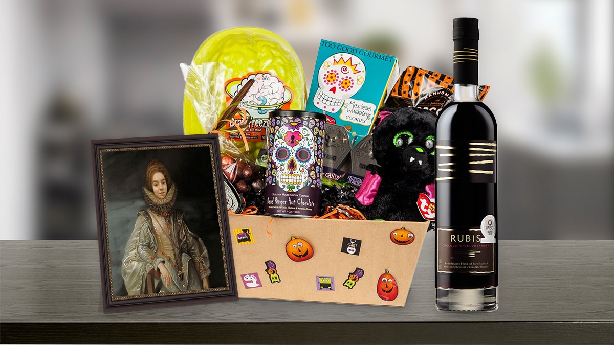 A Halloween gift basket kept on a table containing, wine, candies, cookies, chocolates, and a framed painting of a woman, that can be given as a Halloween gift.