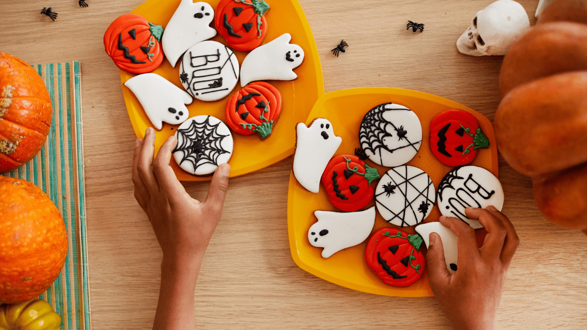 A plate full of Halloween cookies displayed on a Halloween themed table with pumpkins, skull and spiders around the plates. two hands reaching out for the cookies and grabbing them.