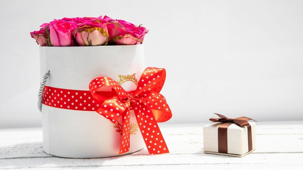 A flower bouquet is kept besides a tiny gift box on a white background.