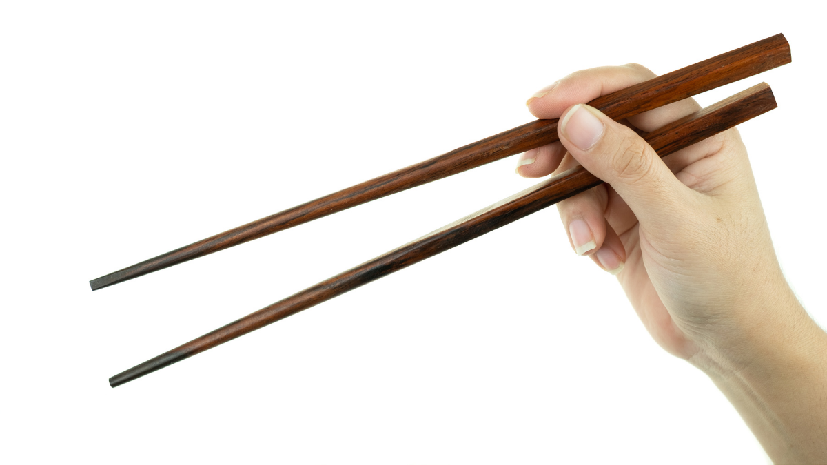 A girl is showing how to hold chopsticks.
