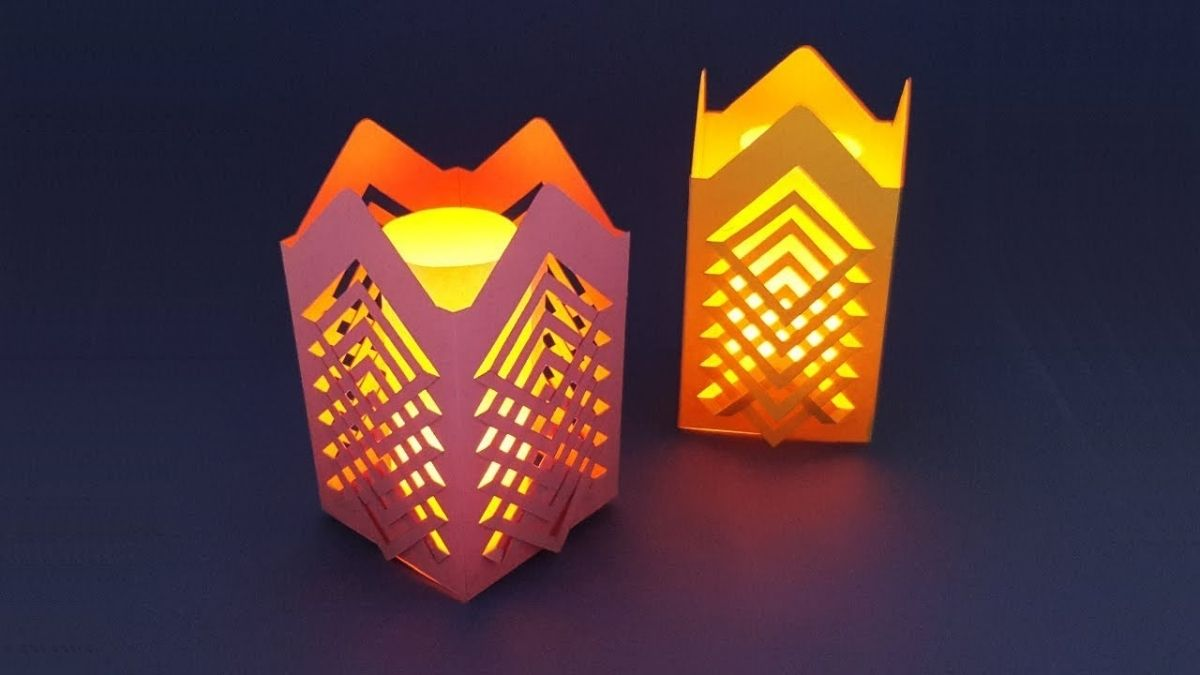 Two handmade lanterns are placed on a plain surface.