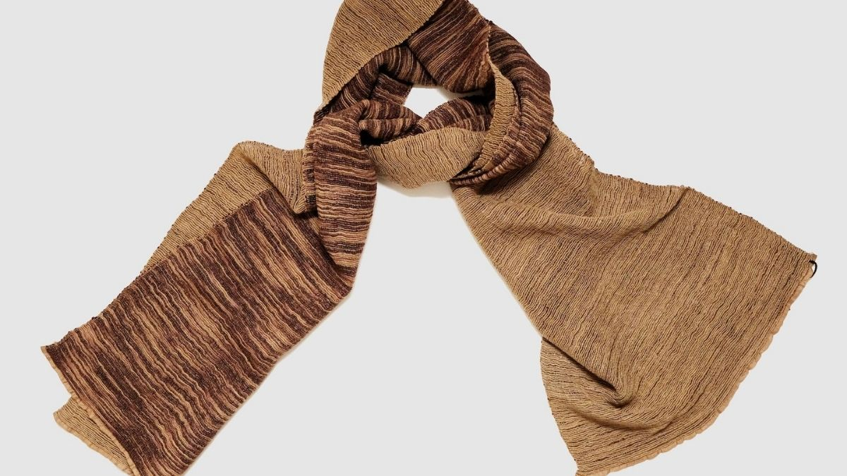 A stylish handmade scarf is lying on a plain white background.