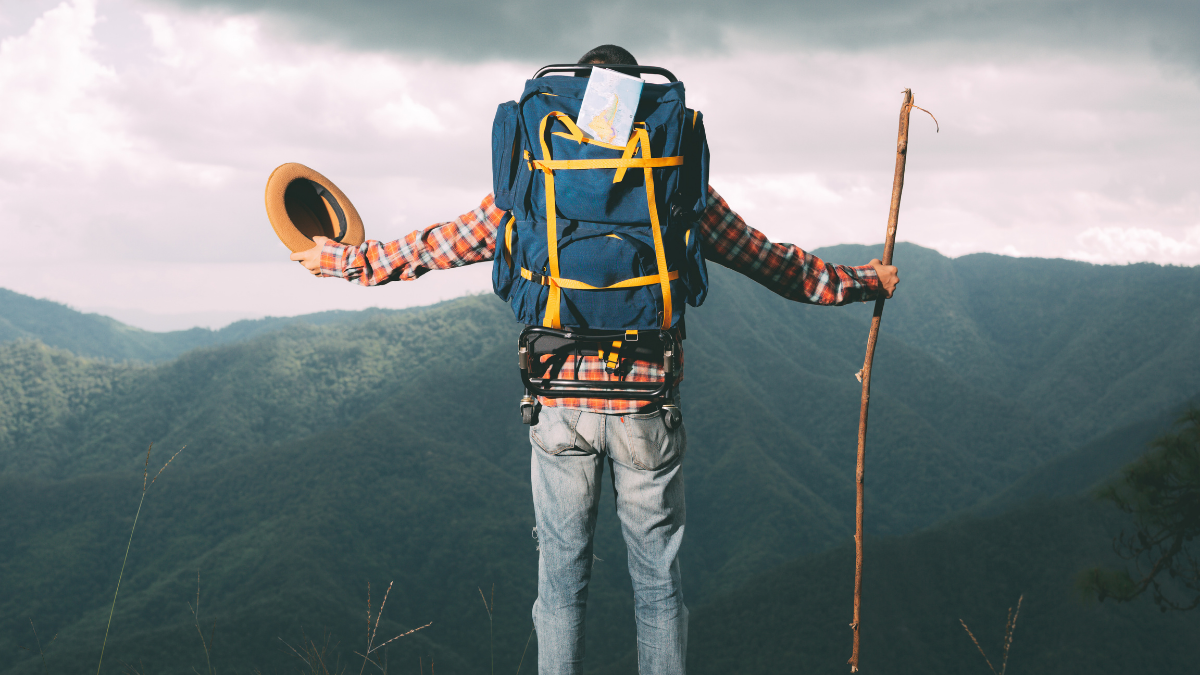 A man with his hiking backpack is seen in open hands on the mountain.