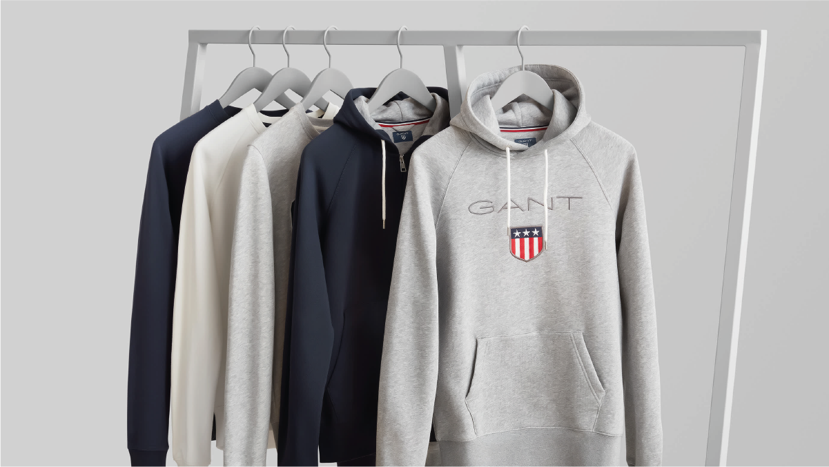 a set of white and black colored hoodies hanged on a stand.