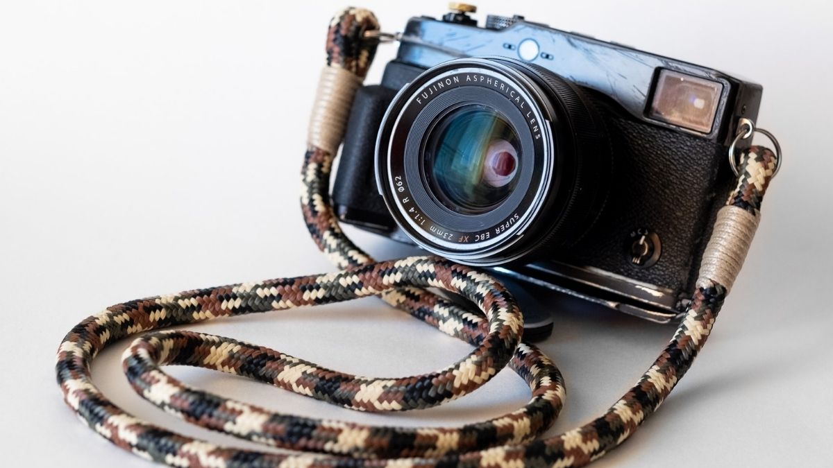 A strap is attached to an old camera.