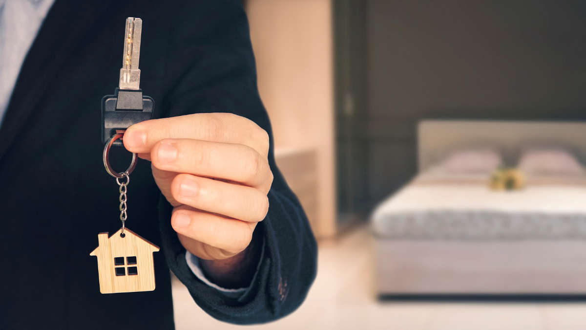 A man in a suit shows a key in a house-shaped keychain.