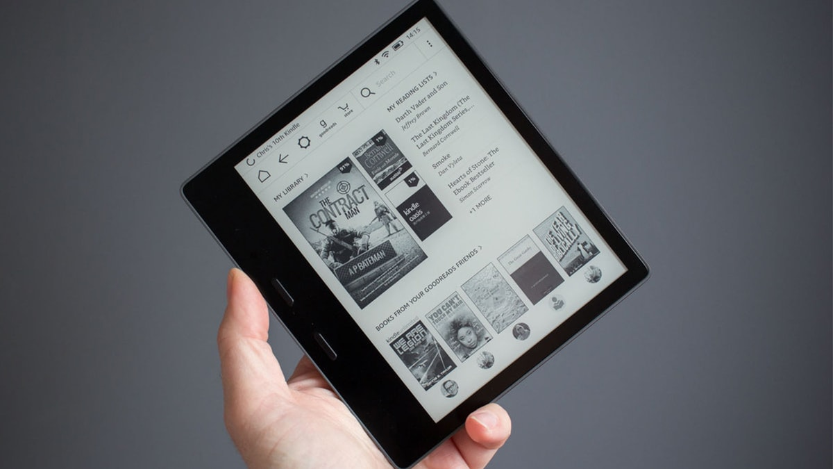 a person holding kindle Oasis in their hand.