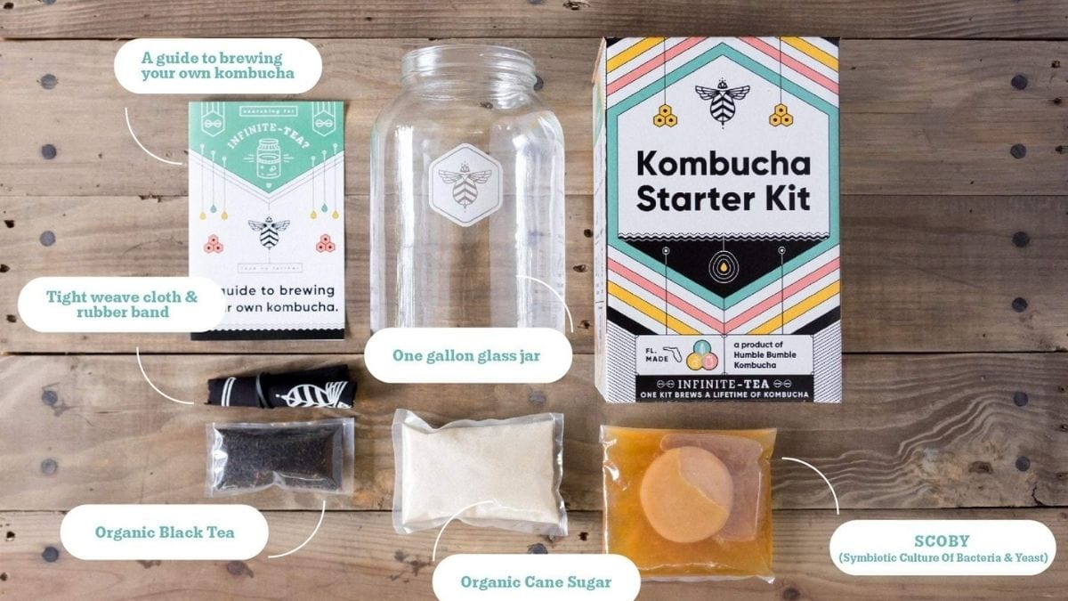 Kombucha starter kit with its contents on a brown wooden table: SCOBY, organic can sugar, organic black tea, one gallon glass jar, Tight weave cloth & rubber bands, a guide booklet.