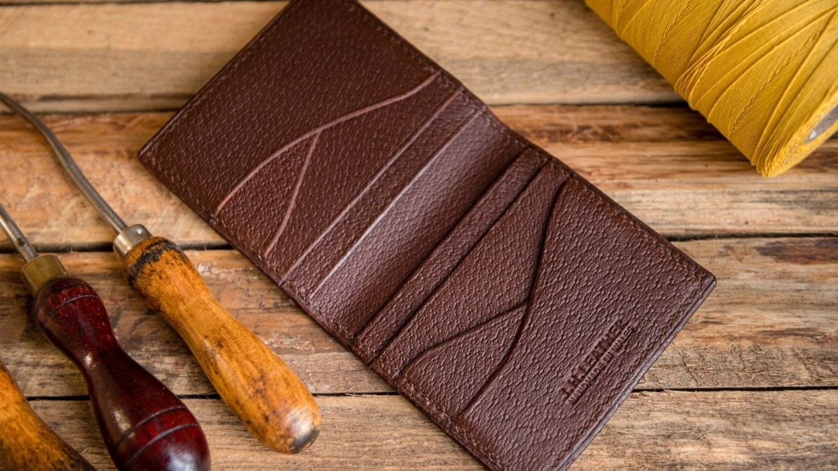 A brown colored leather wallet is placed on a wooden surface.