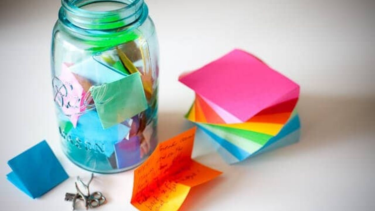 A memory jar filled with letters, sticky notes, and chocolates is placed on a white surface.