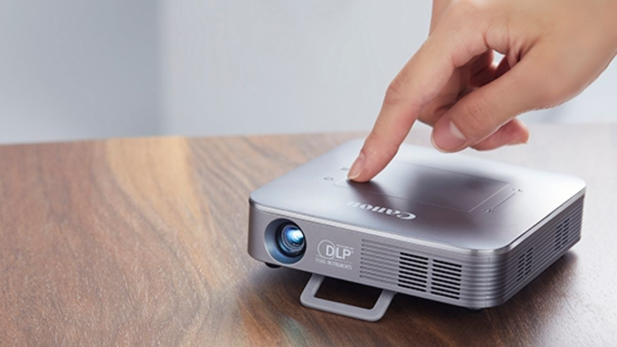 A person starting a mini projector kept on the table.