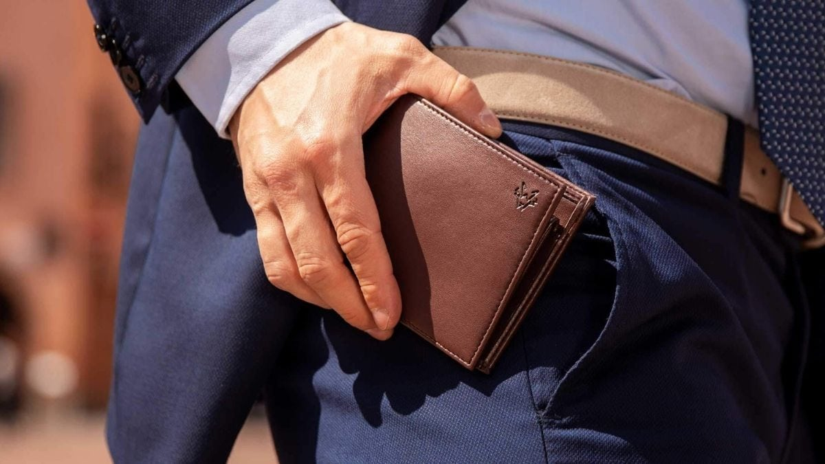 A man wearing formals putting a brown wallet into his pocket.
