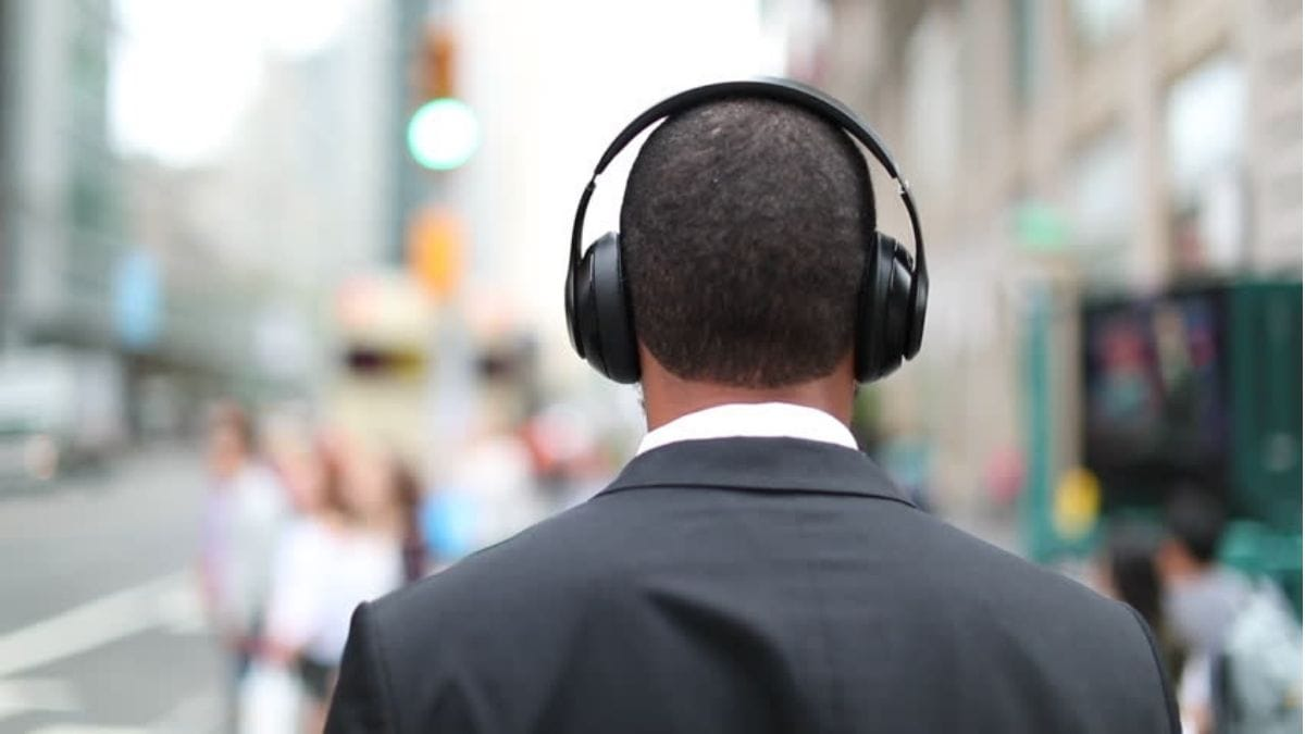 A back-shot of a guy in suit wearing noise cancellation headphones as he walks the streets of a city.