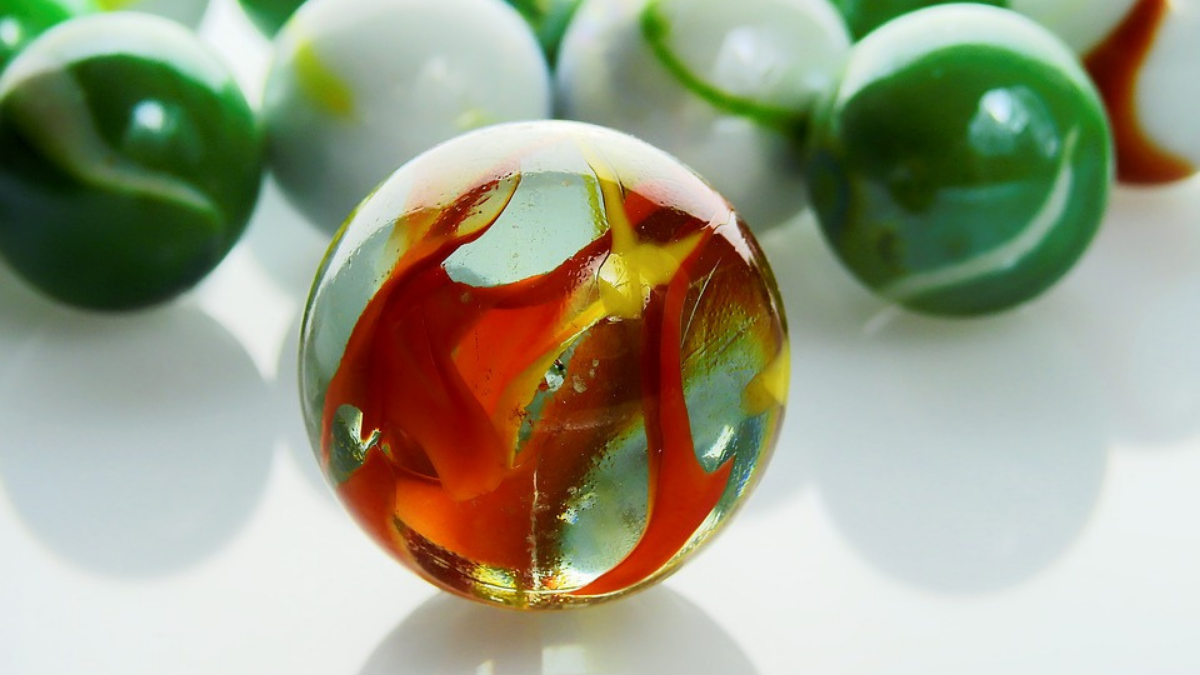 White, Green, and mixed colored paper weights are placed on the white surface.