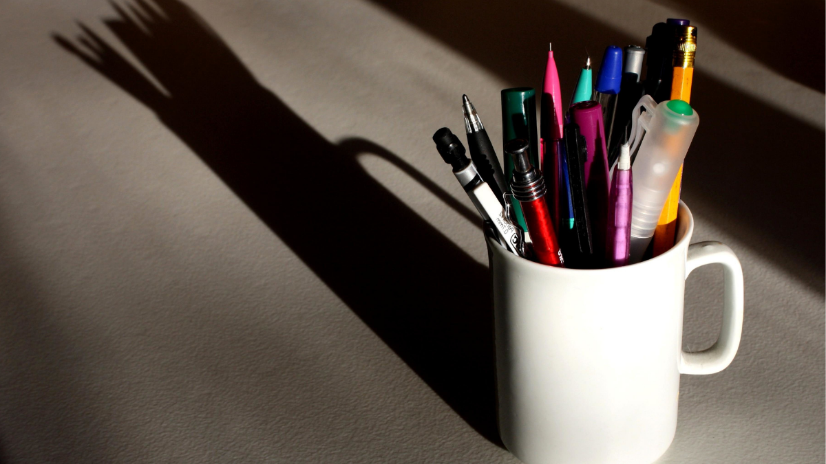 A white plain pen holder's shadow is being seen on the plain surface.