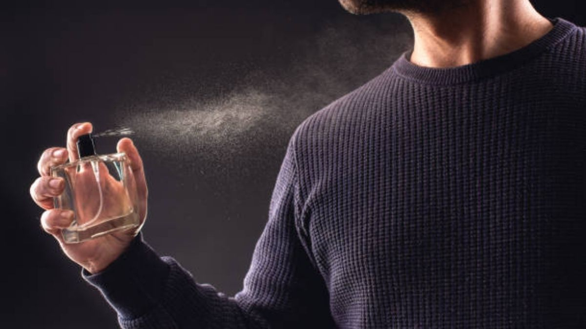 a guy in a purple sleeved shirt spraying the perfume on his shoulder.