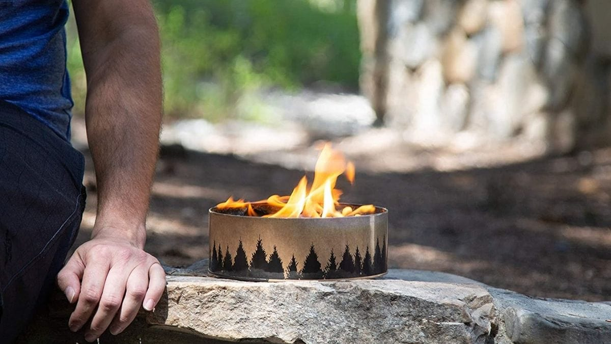 A man sitting by a small portable campfire that is lighted.