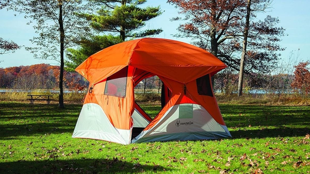 An orange portable camping tent is set outside in the wild.