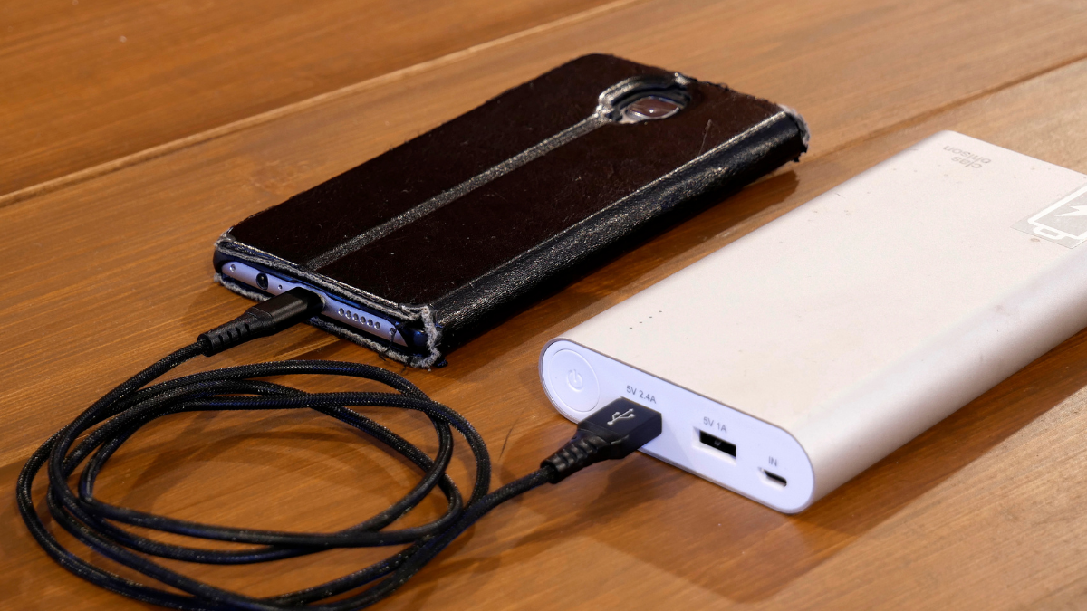 A portable charger is charging the mobile and both of them are placed on wooden surface.